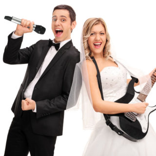 Young bride playing guitar and a young groom singing on microphone isolated on white background
